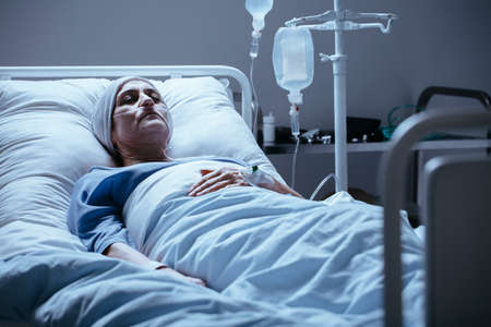 Sick and lonely senior woman with leukemia during chemotherapy in the hospital
