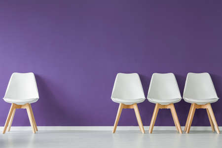 Four white chairs with wooden legs set on an empty purple wall in waiting room interior