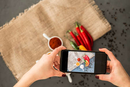 Woman taking a photo of chili peppers and spices with smartphone