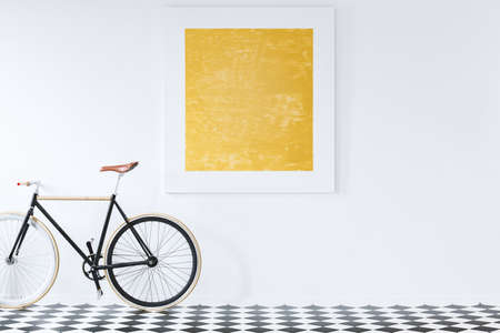 Black bike on checkerboard floor in retro interior with gold painting on white wall Standard-Bild - 103038352