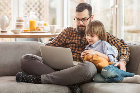 A father teaching a child how to use a computer, sitting with a laptop on the sofa in a spacious living room