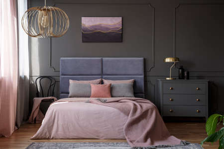 Gold lamp on grey cabinet next to pink bed in elegant pastel bedroom interior with chair