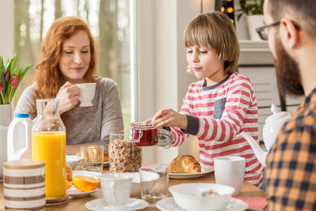 A boy preparing breakfast, eating meal together with his parents at home Stock Photo
