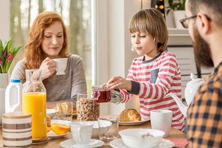 Un niño preparando el desayuno, comiendo junto con sus padres en casa Foto de archivo
