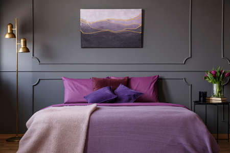 Gold lamp next to purple bed against grey wall with molding and poster in womans bedroom interior