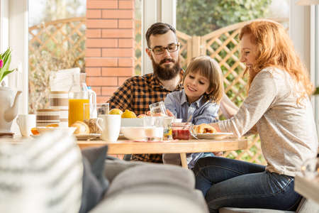Happy, young family spending time together, eating a meal in an arbor Imagens