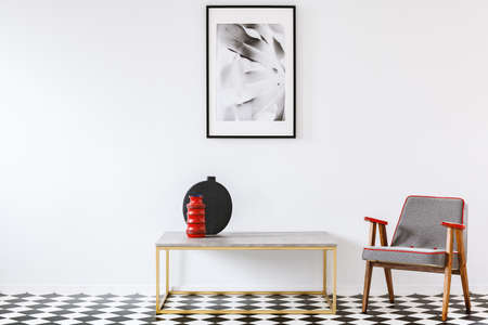 Patterned armchair next to a table with red vase in modern room interior with poster