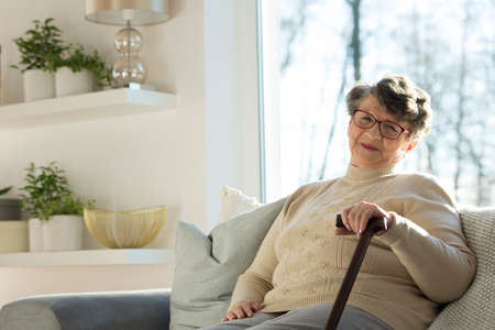 Happy senior woman with a walking stick sitting on a sofa at home Stock Photo