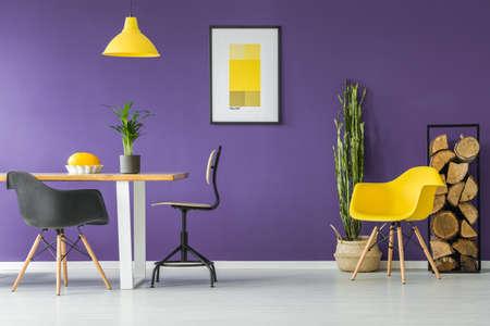 Eettafel, zwarte stoelen, gele poster, planten en brandhout logboekrek in een modern eetkamerinterieur