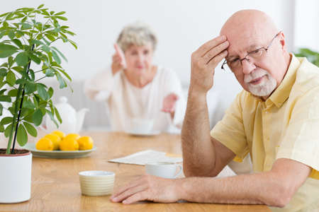 Tired elderly man arguing with his wife in the morning