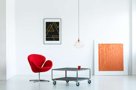 Modern apartment interior with a red armchair, movable coffee table, paintings and lamp Reklamní fotografie