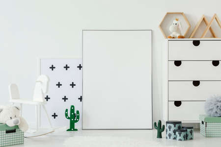 White rocking horse next to empty poster with mockup in kids room interior with cactus motif. Real photo. Paste your poster here Stock Photo