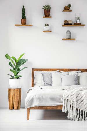 Interior de dormitorio botánico brillante con muebles de madera, sábanas acogedoras, almohadas y plantas naturales en una pared blanca Foto de archivo