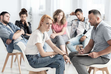Offended girl and psychologist during psychotherapy with rebellious teenagers Stock Photo