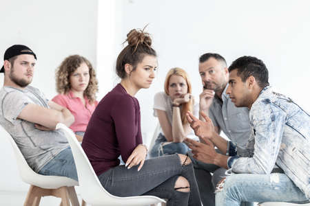 Rebellious girl listening to a friend during meeting for difficult teenagers