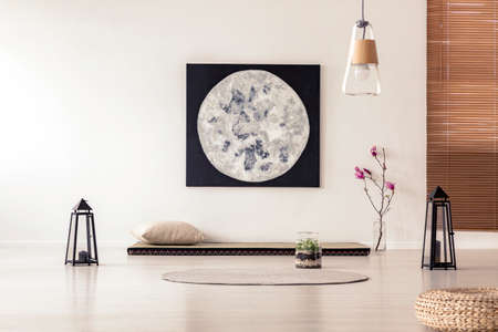 Bright and simple bedroom interior with asian style tatami mat bed, cherry blossom, moon painting on white wall and black lanterns. Real photo