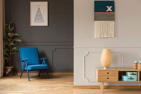 Blue armchair against grey wall with poster and wooden cabinet in living room interior. Real photo