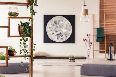 Moon painting above tatami mat bed in japanese style flat interior with ivy on wooden rack and ladder near the window. Real photo Stock Photo