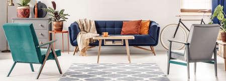 Prawdziwe zdjęcie zielonych i szarych foteli stojących obok wzorzystego dywanu, naprzeciwko niebieskiej sofy z pomarańczowymi poduszkami i drewnianym stołem w kolorowym wnętrzu salonu