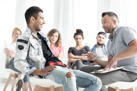 Smiling spanish man talking to a counselor during therapy for young people