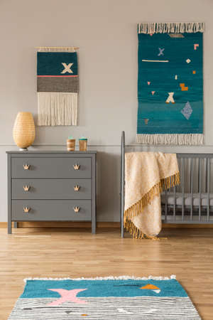 Decor on the wall above grey cabinet and childs bed with blanket in bedroom interior. Real photo