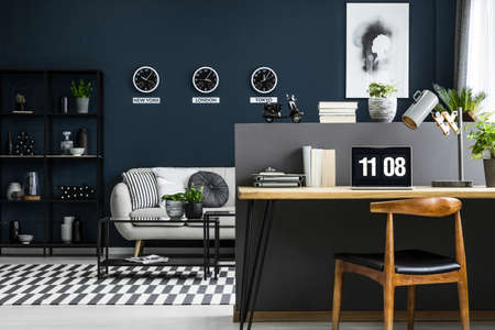 Hairpin desk with books, laptop and lamp in dark industrial living room interior with decor on metal rack, carpet and three clocks on the wall