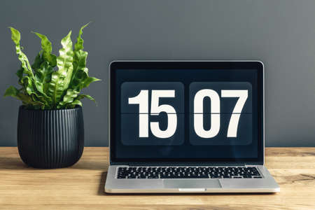 Laptop with clock screensaver placed on a wooden desk with potted plant Stock Photo