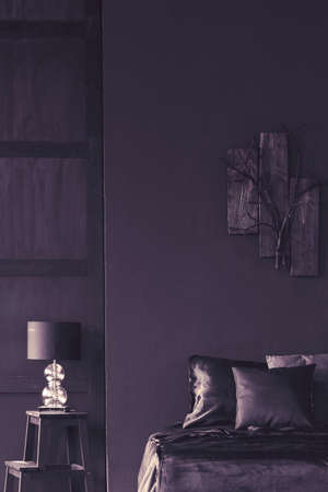 Lamp on a stool next to bed in dark violet bedroom interior with wooden decor on the wall