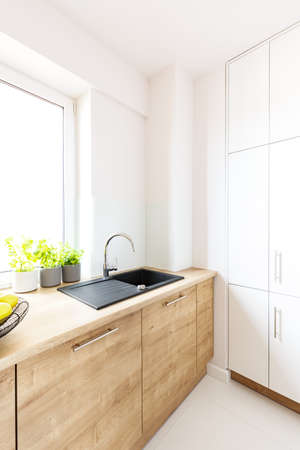 Black sink in wooden countertop in white kitchen interior with window. Real photo