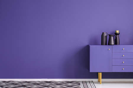 Black vase on violet cabinet against the wall with copy space in minimal living room interior with carpet Imagens