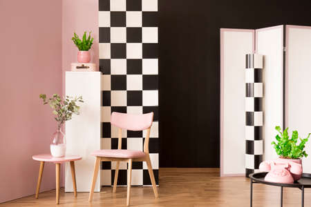 Pink wooden chair against checkerboard wall in living room interior with plant and phone on table 版權商用圖片
