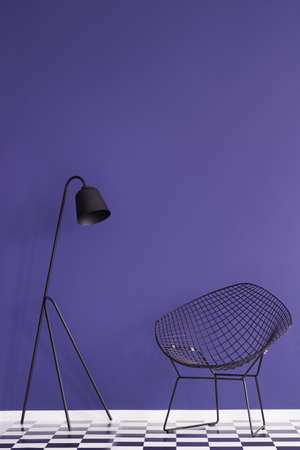 Black lamp next to an armchair in modern violet living room interior with checkerboard floor