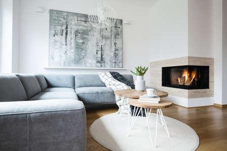 Divano ad angolo grigio con coperte in piedi all'interno del soggiorno nordico bianco con tulipani freschi, libri e tazza di tè sui tavoli a forcina, pittura astratta e camino