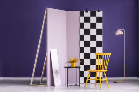 Yellow plant on black table next to a chair against checkerboard wall in colorful studio interior with pink lamp Standard-Bild - 103410669