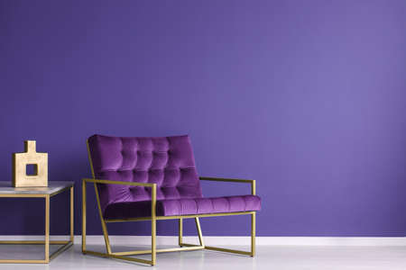 Purple armchair next to a table with gold vase in elegant living room interior with copy space on the wall