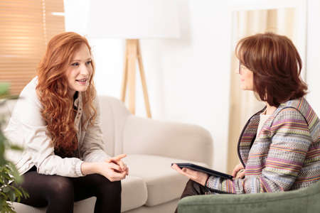 Friendly therapist supporting red-haired woman on how to manage health and life goals