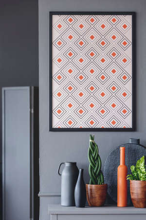 Geometrical poster with orange accents on the wall above plants and vases Stock Photo