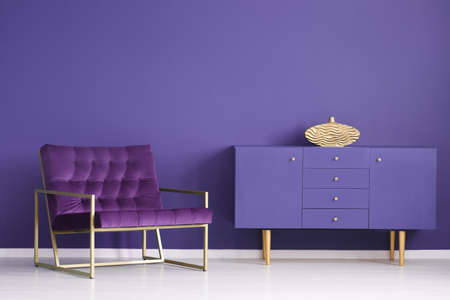 Gold vase on violet cabinet in sophisticated living room interior with purple armchair Stock Photo