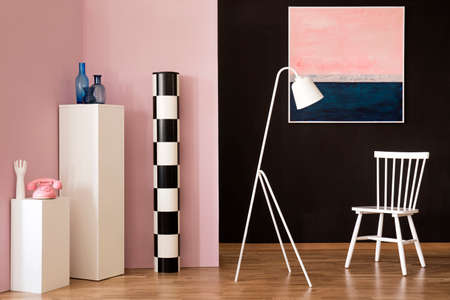 White lamp next to chair in living room interior with pastel painting and pink phone on pedestal