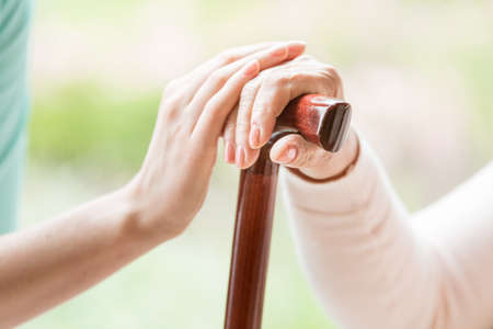 Close-up of caregiver holding hand of a senior person with walking stick against blurred background