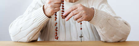 Close-up of religious senior person praying with rosary with cross