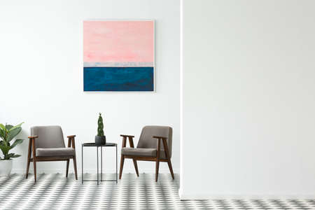 Two grey armchairs, decorative plant on metal table and simple painting hanging on the wall in white open space interior. Empty wall for your product placement
