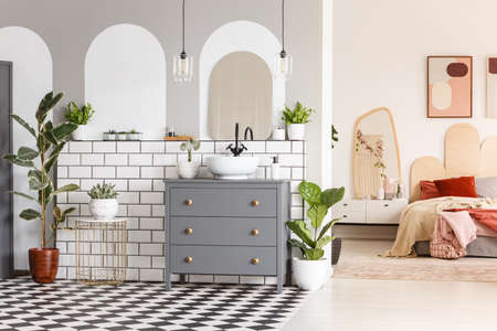 Real photo of a bedroom interior with a bed next to a cupboard with a mirror and two posters on a wall, next to a washroom space with a cupboard, washbasin and mirrors with plants around them