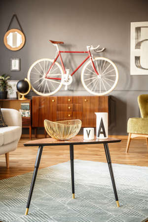 Close view of a black small table with a fruit bowl standing on a green rug with a red bicycle on a sideboard in the background against gray wall in a vintage interior. Real photo.