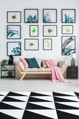 Black and white carpet with geometric pattern placed on the floor in bright sitting room interior with wooden lounge with green and pink cushions, many posters hanging on the wall and end table with glass lamp 스톡 콘텐츠