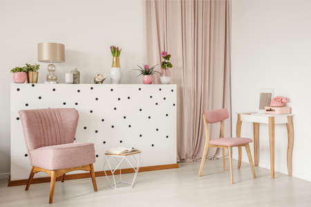 Elegant armchair and an open book by a polka dot wall, wooden vanity table and curtains in a white bedroom interior with dirty pink elements Banque d'images - 103552687