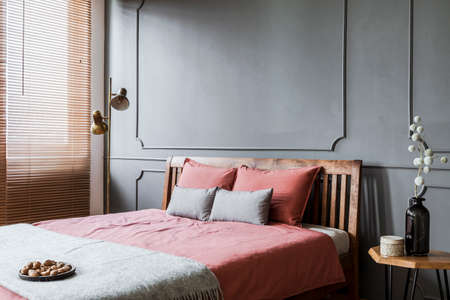 Pink bed against grey wall with molding in womans bedroom interior with gold lamp