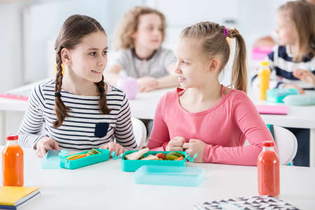 Front view of two girls sitting by a school desk with opened lunch boxes with healthy vegetables and sandwiches. Bottles of orange and tomato juice on a desk. Other children in blurred background Stockfoto
