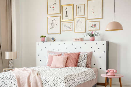 Beautiful white bedroom interior with feminine decor, polka dot pattern, pink accessories and framed sketches gallery on the wall
