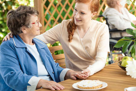 Friendly caregiver supporting happy senior woman during meeting on the terrace